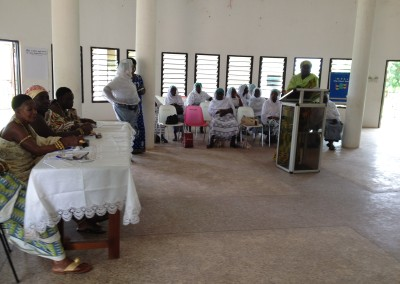 Fatimatu Sulemanu Addresses Consultation (Representatives of Federation of Ghanaian Muslim Women's Associations in Back, Queen Mothers (L))