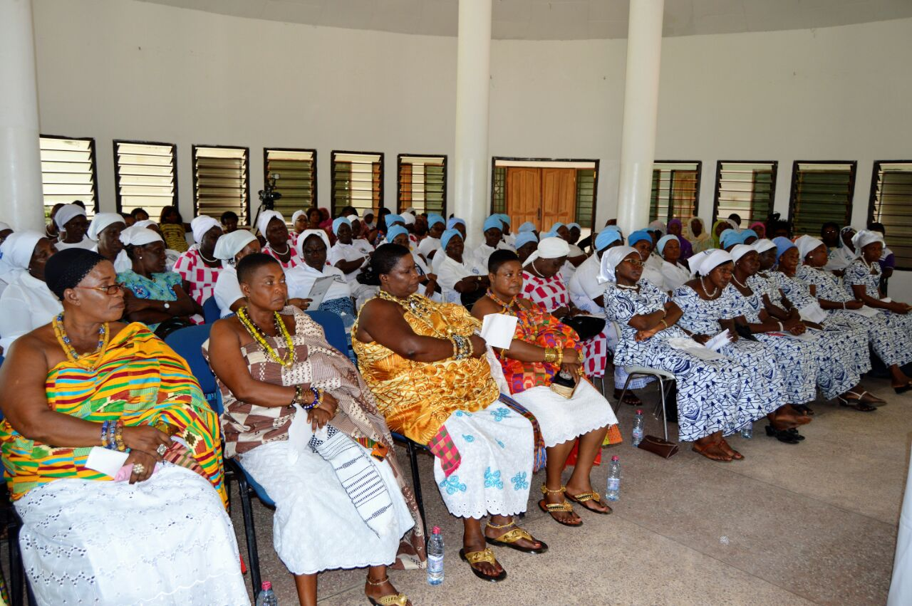 Women from diverse communities listen to conference presenters
