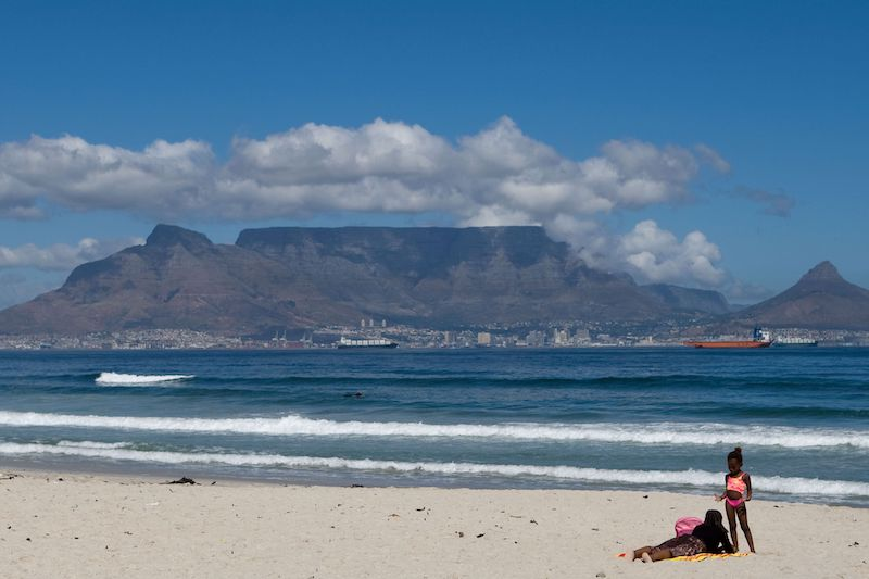Capetown, South Africa beach with an African mother and daughter enjoying the sun.